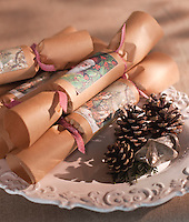 Close up of Christmas crackers and fir cones on a plate