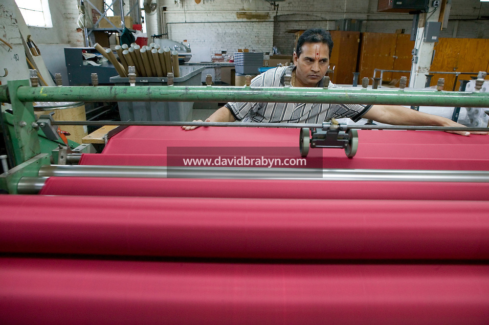 21 June 2005 - Oaks, PA - Suresh Patel checks the rolls of polyester fabric that will be turned into red stripes at the Annin & Co. American flag manufacturing plant in Oaks, PA, USA. Photo Credit: David Brabyn.