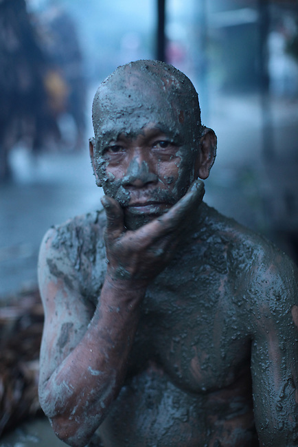 """A man covers himself in mud during the annual Taong Putik, or """"mud people,"""" festival in Bibiclat, on Luzon island, Philippines. The festival honors St. John the Baptist, the village's patron saint, and devotees cover themselves with mud and dress in cloaks made from banana leaves and vines which symbolize the animal skins the saint wore in the Bible.  June 24, 2011."""