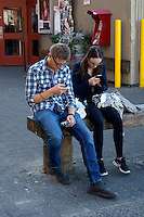 Young man and woman sitting on bench using their cell phones, Vancouver, BC, Canada