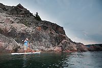 A male stand up paddler on Lake Superior near Marquette Michigan.