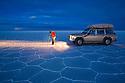 Bolivia, Altiplano, photographer next to 4x4 vehicle in Salar de Uyuni, world's largest salt pan at dusk