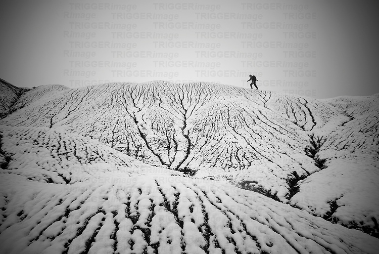 adventure hiker man wearing a backpack strides across the snow covered desert badlands near the small new mexico town of san ysidro, new mexico creating notions of environmental contrasts.  horizontal composition in black and white.