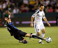 San Jose Earthquakes defender Jason Hernandez (21) attempts a tackle on LA Galaxy midfielder Landon Donovan (10). The LA Galaxy and the San Jose Earthquakes played to a 2-2 draw at Home Depot Center stadium in Carson, California on Thursday July 22, 2010.
