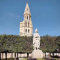 Western bell tower of the Collegiale Notre-Dame de Poissy, a catholic parish church founded c. 1016 by Robert the Pious and rebuilt 1130-60 in late Romanesque and early Gothic styles, in Poissy, Yvelines, France. In front is a statue of Saint Louis or King Louis IX of France, 1951, by Albert-Marius Patrisse, 1892-1964. Saint Louis was born in Poissy in 1214 and baptised in this church in the same year. The Collegiate Church of Our Lady of Poissy was listed as a Historic Monument in 1840 and has been restored by Eugene Viollet-le-Duc. Picture by Manuel Cohen