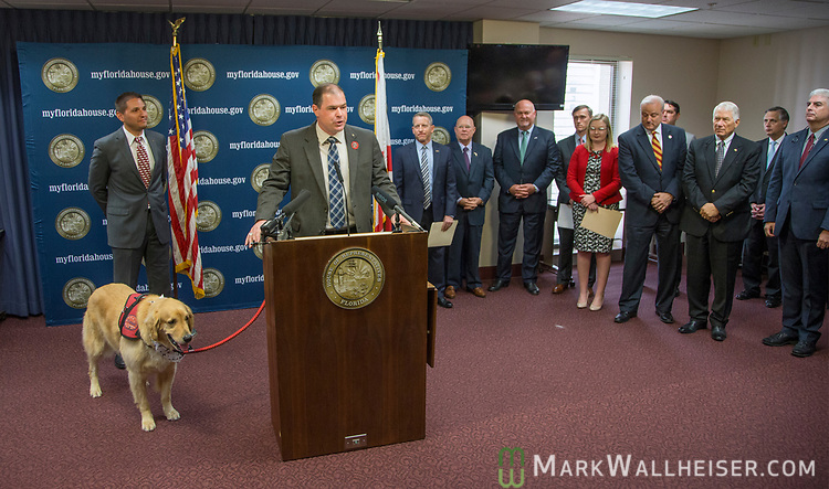 """Brian Anderson, President and CEO of Veterans Alternative and former Green Beret,along with his service dog """"Hero"""", speaks about HB 55 Alternative Treatment Options for Veterans, during a press conference on military-friendly legislation at the Florida Capitol."""