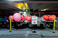 Floats and motorized vehicles used by lifeguards are parked in a hotel garage.