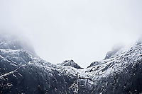 Cloudy weather and snow coveres steep mountain peak, Lofoten islands, Norway