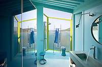 The azure blue walls of this contemporary bathroom with its glassed-in outdoor shower reflect the colour of the sea