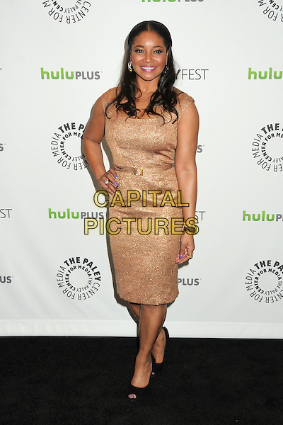 """Tamala Jones.PaleyFest 2012 Presents """"Castle"""" held at The Saban Theatre, Beverly Hills, California, USA, 9th March 2012..full length gold dress hand on hip  belt  hand on hip black shoes peep toe .CAP/ADM/BP.©Byron Purvis/AdMedia/Capital Pictures."""