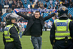 A Sheffield Wednesday fan shows his defiance in front of two police officers dressed in riot gear on the pitch at Hillsborough after the final whistle of the crucial last-day relegation match against Crystal Palace. The match ended in a 2-2 draw which meant Wednesday were relegated to League 1. Crystal Palace remained in the Championship despite having been deducted 10 points for entering administration during the season.