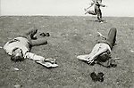 Children run past two men sleeping on the grass in a public park in Barcelona.<br /> [This photograph is currently licensed through GalleryStock - please contact the photographer for details]