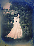 A vintage framed image of a brunette in a white victorian or bridal gown, standing among trees in a thoughtful expression.