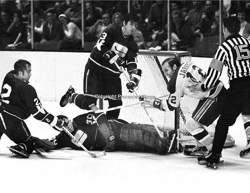 Seals Gary Jarrett tries to score against the Vancouver Canucks, goalie Dunc Wilson, #3 Pat Quinn and #2 Gary Doak.  (1971 photo by Ron Riesterer)