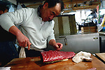 "A wholesaler at the world's biggest fish Market in Tsukiji, Tokyo cuts up pieces of tuna at his store at the market. More than 2,300 tons of fish -- about one-third of the total consumed in Japan -- passes through Tsukiji each day and the market offers more than 450 varieties of marine products. The market, which dates back almost 75 years, is slated to move to a high-tech site on a man-made island in Toyosu, which is well-documented as being contaminated with benizine. Not that Tsukiji is much better off -- many buildings in the aging site are stuffed with asbestos. ""Choose your poison,"" says one Tsukiji official. The new site, which the government plans to be readied by 2012, will be significantly larger, with more room for off-loading and for sellers to display their goods. The current location, says one official, is too cramped and collisions between motorised carts and pedestrians means accidents occur almost daily. Meanwhile, with fish sales down, it is becoming more difficult to justify Tsukiji's prime location and property developers are keeping a close watch on Tsukiji land, which is just a few blocks from the ritzy Ginza district of Tokyo, where per-meter land prices are among the highest in the world...The move to the new Toyosu location, meanwhile, has been at the center of heated debate -- clean-up operations alone are estimated to cost ¬?67 billion (around US$660 million), with a further ¬?450 billion to build a new marketplace. Big wholesalers favour the move, but the 1,600-plus merchants mostly are against it. Yoshiharu Kikuraku, a Tsukiji storeowner who began working at the market 60 years ago, expresses bewilderment at the plans, saying that the name Tsukiji itself has become synonymous with the world's best and most eclectic selection of fish. ""This place has a long tradition. Why break it and start from scratch all over again?"" he says."