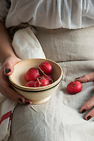 Woman holding bowl of radishes