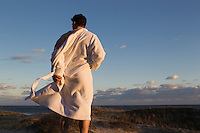 man taking off his robe at the beach in The Hamptons