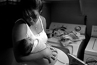 Melanie Dahlan looks at her three-day-old son Kai while doing laundry. Bringing life into the world. A young couple experiences the birth of their first child.
