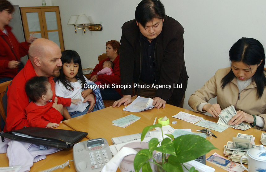 New adoptive parents hands over various fees totalling 3,700 US$, for their newly adopted baby girls, to Government officials in Changsha, Hunan, China.