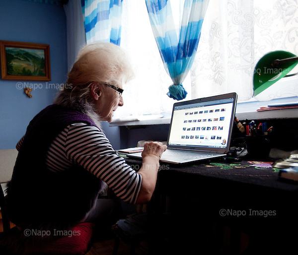 WARSAW, POLAND, NOVEMBER 2011:.Wika Szmyt, 74 year old DJ working on her computer at home..Wika is famous in Poland for being the oldest DJ. Twice a week she runs discos at the Bolek club in Warsaw, frequented mainly by the pensioners..(Photo by Piotr Malecki/Napo Images)..WARSZAWA, LISTOPAD 2011:.DJ Wika pracuje na komputerze w domu. Wika Szmyt, 74-letnia DJ jest znana jako najstarsza didzejka w Polsce. Dwa razy w tygodniu prowadzi dyskoteki w klubie Bolek, na ktore przychodza glownie emeryci..Fot: Piotr Malecki/Napo Images.***ZAKAZ PUBLIKACJI W TABLOIDACH I PORTALACH PLOTKARSKICH*** .*** Zdjecie moze byc uzyte w prasie, gdy sposob jego wykorzystania oraz podpis nie obrazaja osob znajdujacych sie na fotografii ***.
