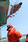 A rescue basket is lowered to the deck of a Coast Guard Auxiliary vessel by a United States Coast Guard HH-65C Dolphin helicopter. The helicopter and crew, based at U.S. Coast Guard Air Station San Francisco, was on a practice mission with the Coast Guard Auxilary to maintain search and rescue proficiency. Photographed 04/08