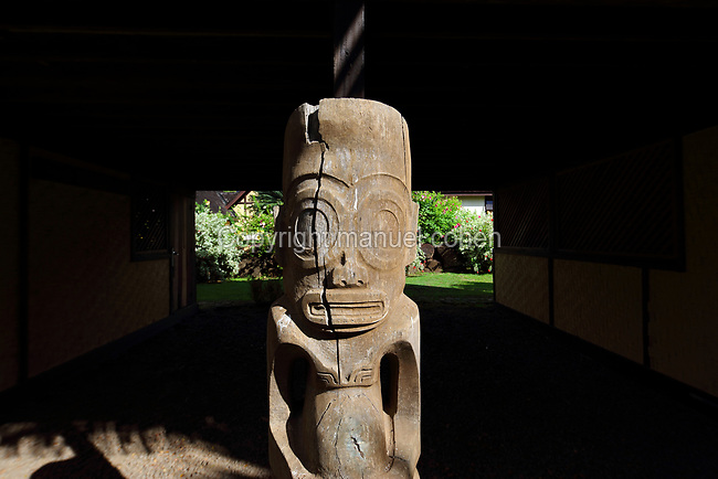Carved wooden tiki sculpture outside the reconstruction of the Maison du Jouir or House of Pleasure, a traditional 2-storey hut and home to French artist Paul Gauguin, 1848-1903, from 1901 to his death, now part of the Paul Gauguin Cultural Center, a museum which opened in 2003, in Atuona, on the island of Hiva Oa, in the Marquesas Islands, French Polynesia. Tiki sculptures represent Ti'i, a half-human half-god ancestor who is believed to be the first man. Tiki often have a huge head, symbolising power, and big eyes symbolising knowledge. Tiki are respected and are often placed outside houses as protective statues. Picture by Manuel Cohen