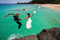 """A couple in wedding attire jumping off the Waimea """"jump rock"""" on the North Shore of O'ahu."""