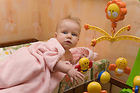 Caucasian Infant Playing with Hanging Bed Toys