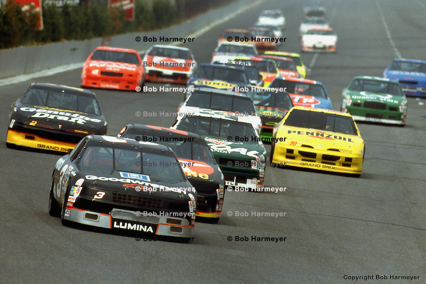 LONG POND, PA - JUNE 16: Dale Earnhardt leads a group of cars into Turn 1 during the Champion Spark Plug 500 on June 16, 1991, at the Pocono International Raceway near Long Pond, Pennsylvania.