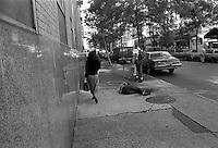 Pedestrians walk around a sleeping homeless man. Street scenes, manhattan, New York, USA