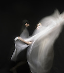 A young woman moving with a veil of white fabric