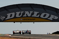A pair of LMP cars crest the hill under the Dunlop bridge during the 2002 24 Hours of Le Mans.
