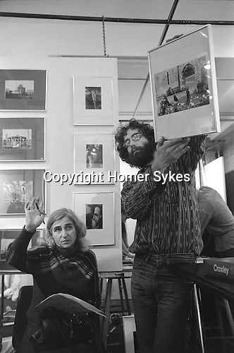 The Photographers Gallery Great Newport Street London 1971.&quot;Co Optic&quot;  Christmas Print Auction. Dorothy Bohm bidding for a Tony Ray Jones print being held up by the photographer Bob Mazzer.