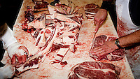 Staff butcher a beef carcass at a small family owned slaughter and meat packing company in Mead, Kansas. At this firm they typically slaughter ten animals each day but is one of only a few such sized companies in a region dominated by four giant meat packing plants that kill and process between five and six thousand cattle a day.