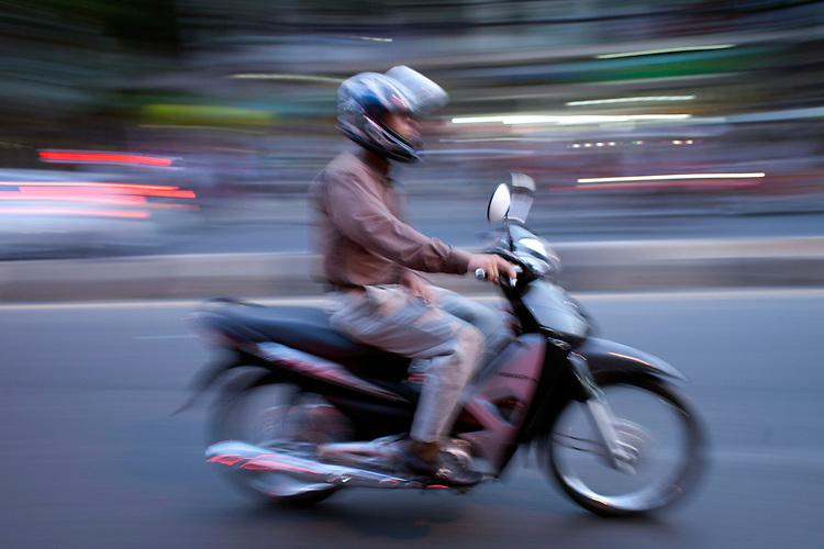 Motorcycle rider in Phnom Penh, Cambodia. <br /> <br /> Photos &copy; Dennis Drenner 2013.