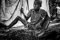 A boy uses a machete to dig a hole for erecting a tent in a camp for those displaced by the recent earthquake in Petionville, outside Port-au-Prince, Haiti.
