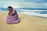 Mother who lost her three children to the sea when the tsunami hit   <br /> Batticola, Sri Lanka 2005.<br /> Of the 8,000 residents of Batticaloa, 5,000 died. That&rsquo;s 60 percent of its population. The once-thriving beach-front village was surrounded by a lagoon so there was nowhere to run when the giant wave hit, just into more water. Saris and clothing were left embedded in the barbed wire set up to protect against wild animals, where many of the bodies were trapped in its grip. A few remnants were scattered: cooking pots, photographs with cracked glass, clocks stopped when the wave hit at 9:22, Buddhist statues which mysteriously remained standing. But mostly there was just rubble. Everywhere had its own ghosts. <br /> I viewed the beach, cluttered with personal effects. Human bones had started to wash up. A woman walked alongside me who appeared to be in shock. As I turned to ask if she was all right she began madly gesticulating toward the sea, indicating that it had taken her two children. She, as so many I encountered, now lived with the image of seeing her family swept away and struggled with the profound guilt of being unable to hold onto her children. Beside herself with anguish she attempted to throw herself into the ocean. I pulled her back and held her as she wept. Inconsolable, she buried her face in the sand. Death is certainly more integrated with life in this part of the world, but there was no quantifying the universality of a mother&rsquo;s pain.