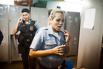 Pacifying Police officer Elaine Soares Concei&ccedil;&aacute;o, right, prepares for her shift, in Complexo do Caju, Rio de Janeiro, Brazil, on Friday May 10, 2013.<br /> <br /> In the early hours of Sunday, March 3, 2013, about 1,400 Brazilian security forces occupied 13 communities during a joint public security operation to install a Pacifying Police Unit (UPP) in two Rio de Janeiro favelas, Complexo do Caju and Barreira do Vasco. Elite police units backed by armored military vehicles and helicopters invaded the neighborhood in an on-going policing program aimed to drive violent and heavily armed drug gangs out of Rio's poor communities, where the traffickers have ruled for decades. For the community of Caju, that is ADA (Amigos de Amigos) and CV (Comando Vermelho).