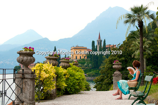 A woman looks at the view while sitting on a bench in the gardens of the Villa Monastero in Varenna, Italy on Lake Como