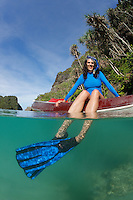qp0418-D. woman (model released) explores karst islands by snorkel and kayak during surface interval between scuba dives. Raja Ampat, Indonesia, tropical Indo-Pacific Ocean.<br /> Photo Copyright &copy; Brandon Cole. All rights reserved worldwide.  www.brandoncole.com<br /> <br /> This photo is NOT free. It is NOT in the public domain. This photo is a Copyrighted Work, registered with the US Copyright Office. <br /> Rights to reproduction of photograph granted only upon payment in full of agreed upon licensing fee. Any use of this photo prior to such payment is an infringement of copyright and punishable by fines up to  $150,000 USD.<br /> <br /> Brandon Cole<br /> MARINE PHOTOGRAPHY<br /> http://www.brandoncole.com<br /> email: brandoncole@msn.com<br /> 4917 N. Boeing Rd.<br /> Spokane Valley, WA  99206  USA<br /> tel: 509-535-3489