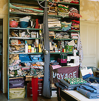 Myriam Balay Devidal's studio in her apartment in Nimes. Myriam is one half of Les Copirates, a French design duo, and here she creates her unique pieces and objects. A free-standing shelving unit is full of fabrics and haberdashery