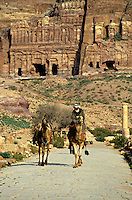 Man riding a camel down a cobblestone road near the entrance to the Royal Tombs carved into the cliffs at Petra, Jordan.