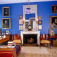 Walls painted a bright contemporary blue create a stunning background for antique paintings and furniture in this St Petersburg living room