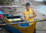 Rodel Banoson ties a cross member on his outrigger canoe on Jinamoc Island, part of the municipality of Basey in the Philippines province of Samar that was hit hard by Typhoon Haiyan in November 2013. The storm was known locally as Yolanda. The ACT Alliance has been providing a variety of assistance to survivors here, and is planning a long-term rehabilitation program with residents.