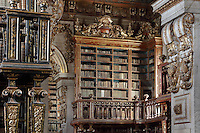 Bookshelves with Chinese motifs, lacquer and gilding by Manuel da Silva, in the Black Room (left), looking through to the Red Room of the Joanina Library, or Biblioteca Joanina, a Baroque library built 1717-28 by Gaspar Ferreira, part of the University of Coimbra General Library, in Coimbra, Portugal. The Casa da Livraria was built during the reign of King John V or Joao V, and consists of the Green Room, Red Room and Black Room, with 250,000 books dating from the 16th - 18th centuries. The library is part of the Faculty of Law and the University is housed in the buildings of the Royal Palace of Coimbra. The building is classified as a national monument and UNESCO World Heritage Site. Picture by Manuel Cohen