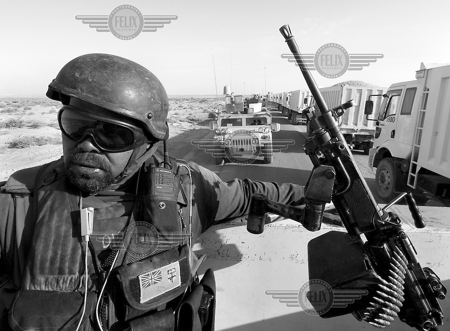 A Fijian private security operator from the British company ArmorGroup sits in the gun turret of a vehicle escorting a supply convoy near Al Asad air base on October 17, 2006.  The coalition forces and civilian administration in Iraq depend heavily on thousands of controversial security contractors to support their reconstruction efforts and military operations.