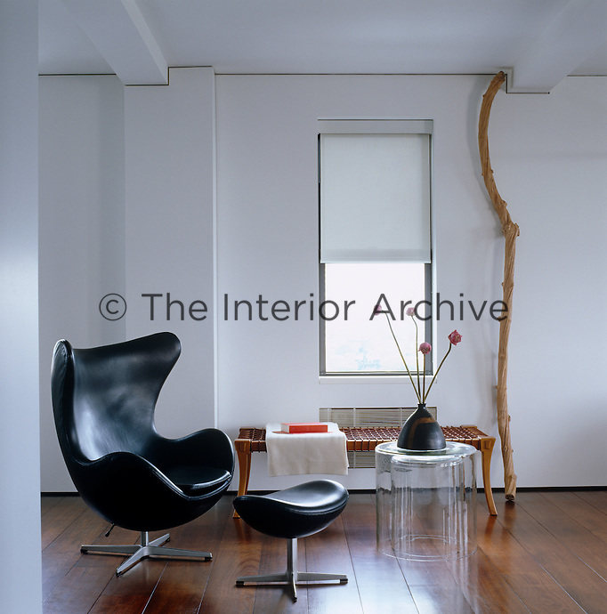 A black leather Arne Jacobsen Egg chair and footstool in the open-plan living area