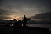 A vendor is silhouetted against the setting sun as he walks with his cart along the bay in Puerto Princesa, Palawan in the Philippines. <br /> Photo: Sanjit Das/Panos for Greenpeace