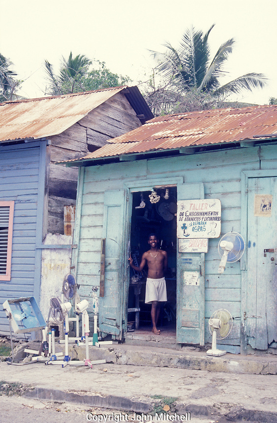 Man standing in front of his electrical repair shop, Barahona, Dominican Republic