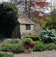 A vernacular stone building forms part of the wall that surrounds the garden